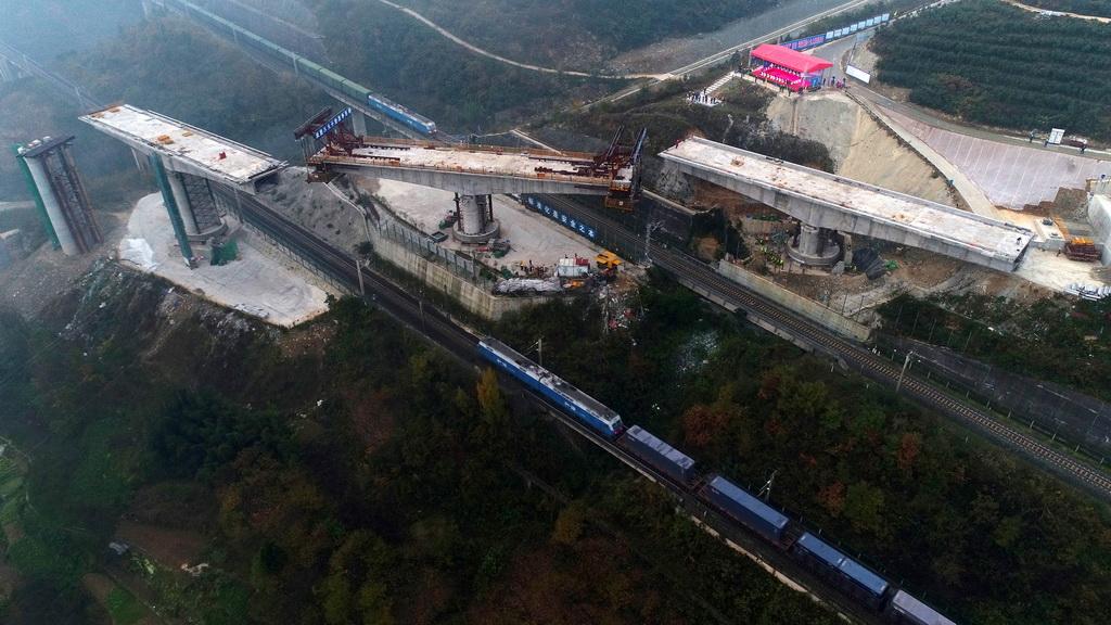 11月7日,襄渝铁路线上下行列车同时经过汉十高铁三墩转体桥施工现场。 新华社发(陶德斌 摄)