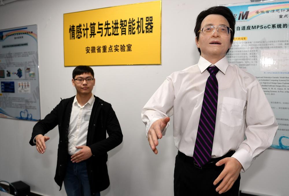 """11月16日,合肥工业大学研究人员和情感机器人""""想想""""进行姿态同步互动。"""