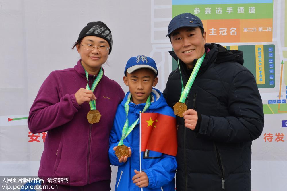 2017年11月19日,参加青岛海上国际马拉松体验赛的家庭在赛后展示奖牌.