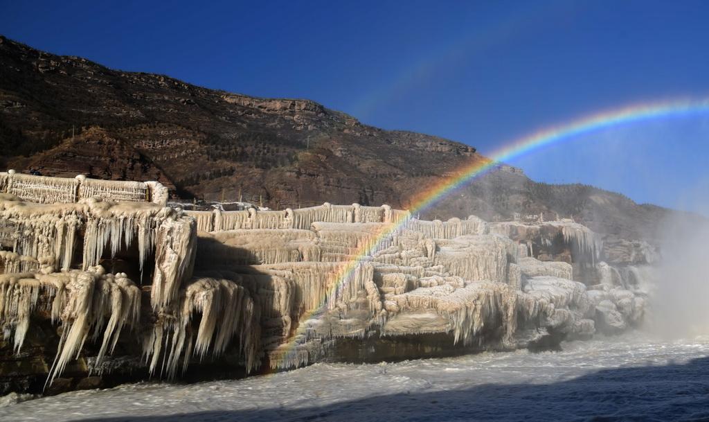12月17日在山西吉县黄河壶口瀑布拍摄的冰瀑彩虹景观。 新华社发(吕桂明 摄)