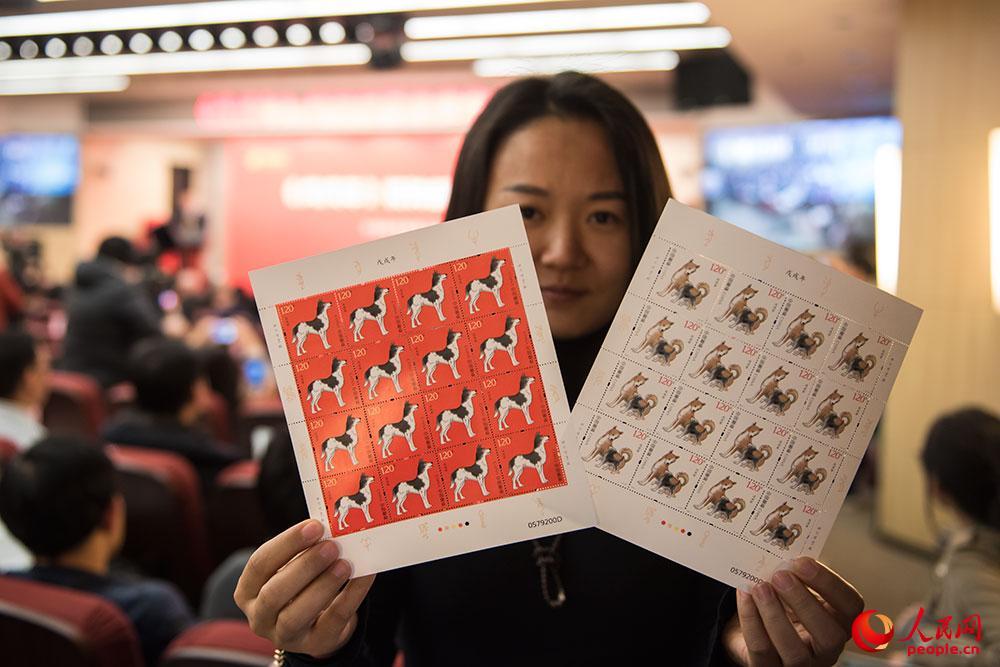 记者正在展示《戊戌年》生肖邮票。