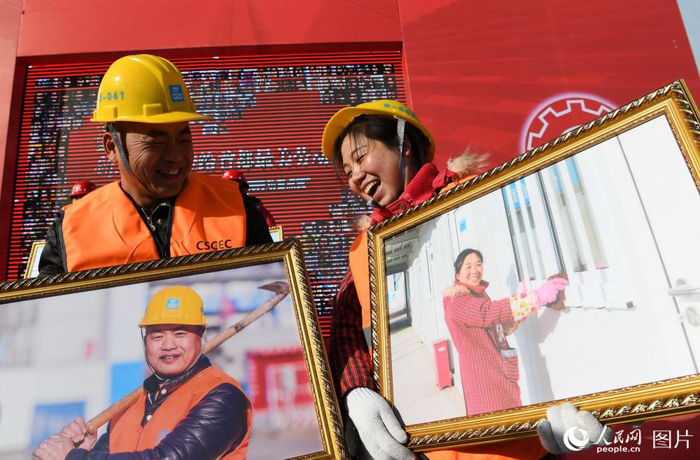 1月9日,北京城市副中心一处安置房工地,农民工夫妇黄春平(左)和曾风在比拼谁的照片更美。(徐烨/摄)