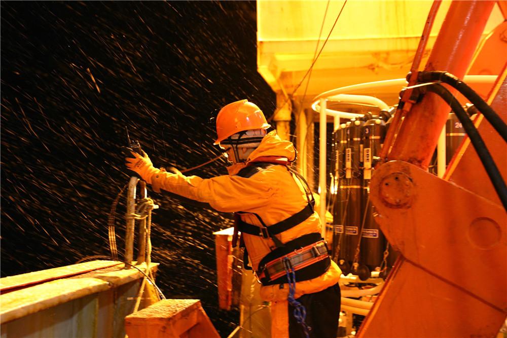 科考队员进行舯部甲板布放CTD(海水温盐深剖面仪)采水作业(3月2日摄)。