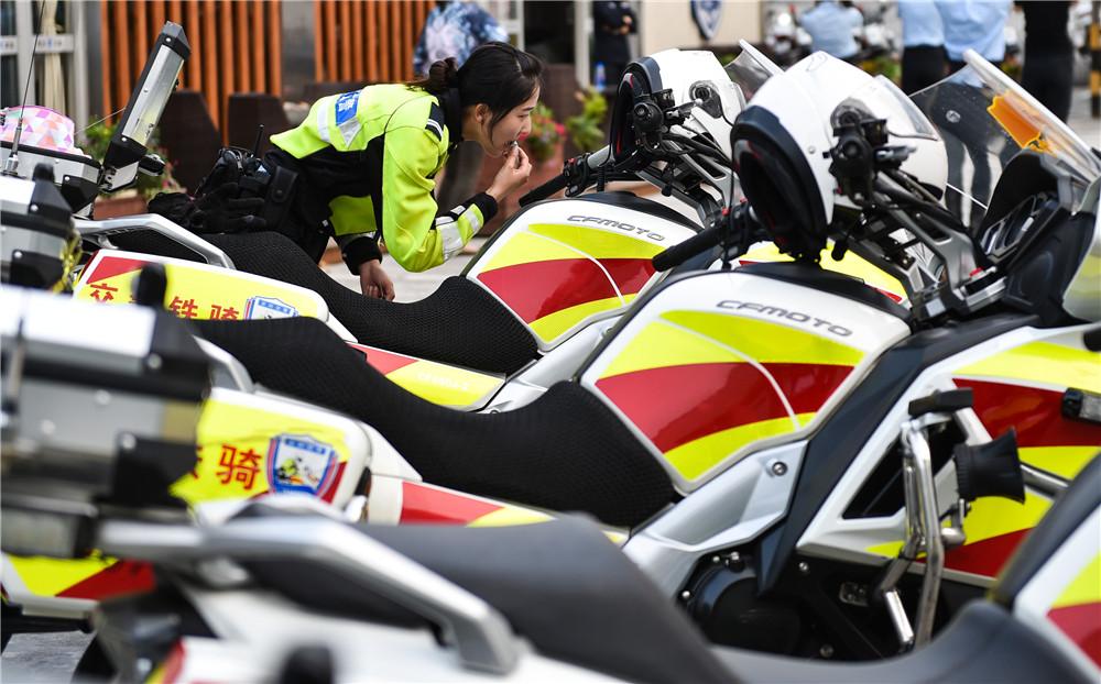 3月7日,女铁骑陈荣辉在休息间隙对着摩托的后视镜涂抹唇膏。