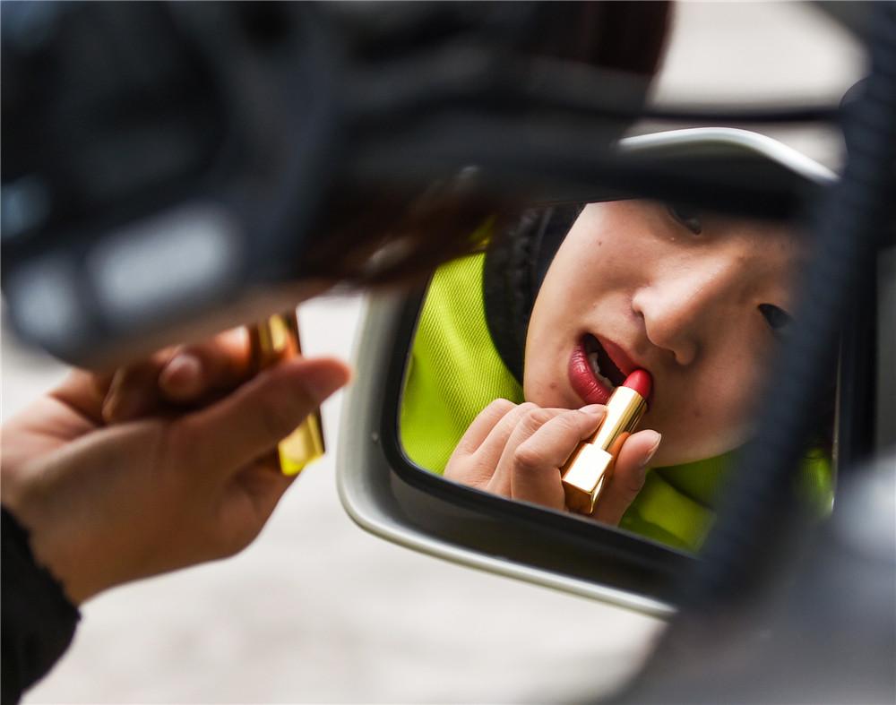3月7日,女铁骑党雪莲在出勤前对着摩托的后视镜擦口红。