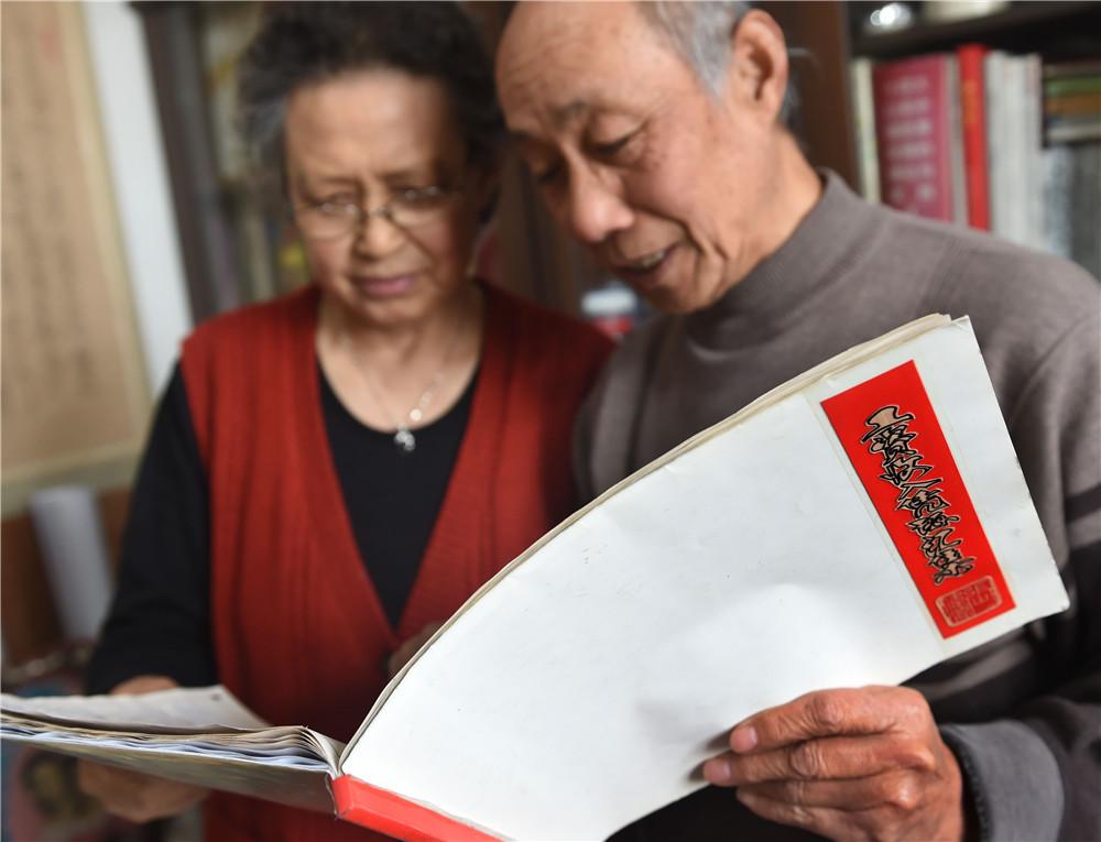 青岛退休教师张伟源和老伴在家中翻看《工资收入凭证汇集》(3月8日摄)。