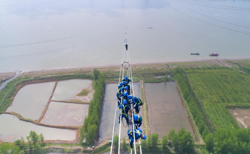 4月15日,在安徽省无为县高沟镇,工人们在昌古特高压长江大跨越工程跨越塔导线上进行高空作业(无人机拍摄)。新华社记者 郭晨 摄