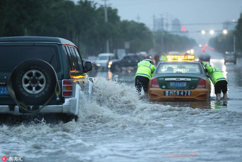 山西运城:暴雨如注马路内涝成海 交警水中推车如推船