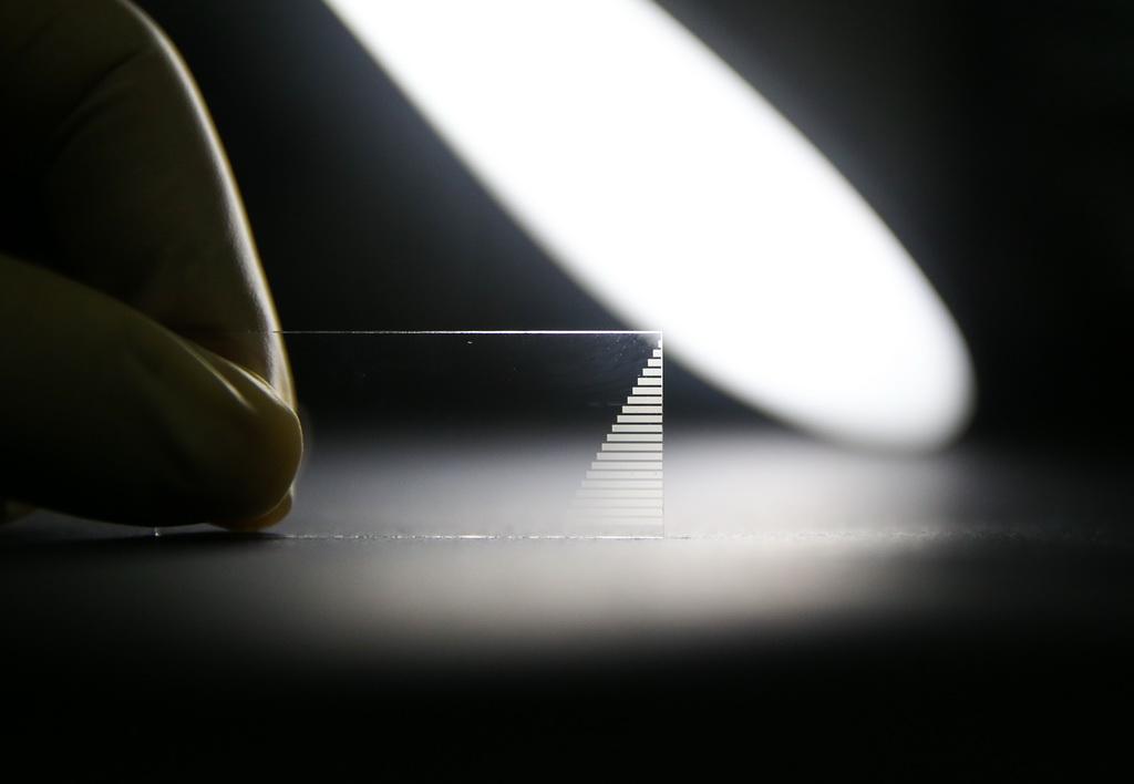 5月15日,在上海交通大学实验室内,金贤敏教授展示制备的芯片。新华社记者丁汀摄