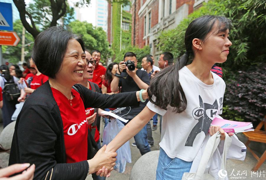 """2018年6月7日,上海格致中学,高考开考前,送考老师身着champion字样的红衣寓意""""开门红"""",给考生加油鼓劲。王初 摄"""