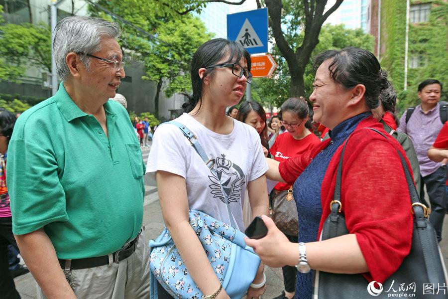 """2018年6月7日,上海格致中学,高考开考前,送考老师身着红衣寓意""""开门红"""",给考生加油鼓劲。王初 摄"""