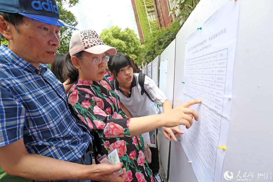 2018年6月7日,上海格致中学,考生和家长查看考场。王初 摄