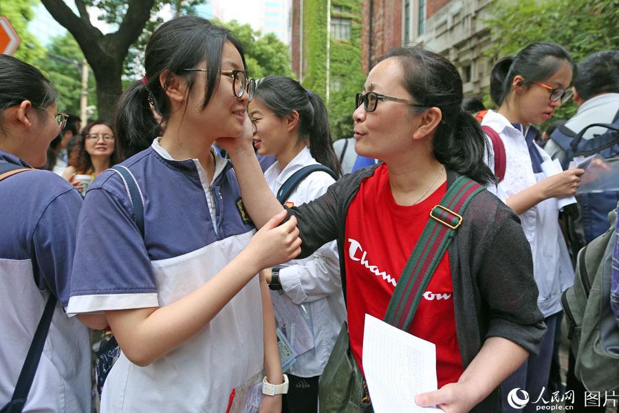 """2018年6月7日,上海格致中学,高考开考前,送考老师身着印有champion字样的红衣寓意""""开门红"""",给考生加油鼓劲。王初 摄"""