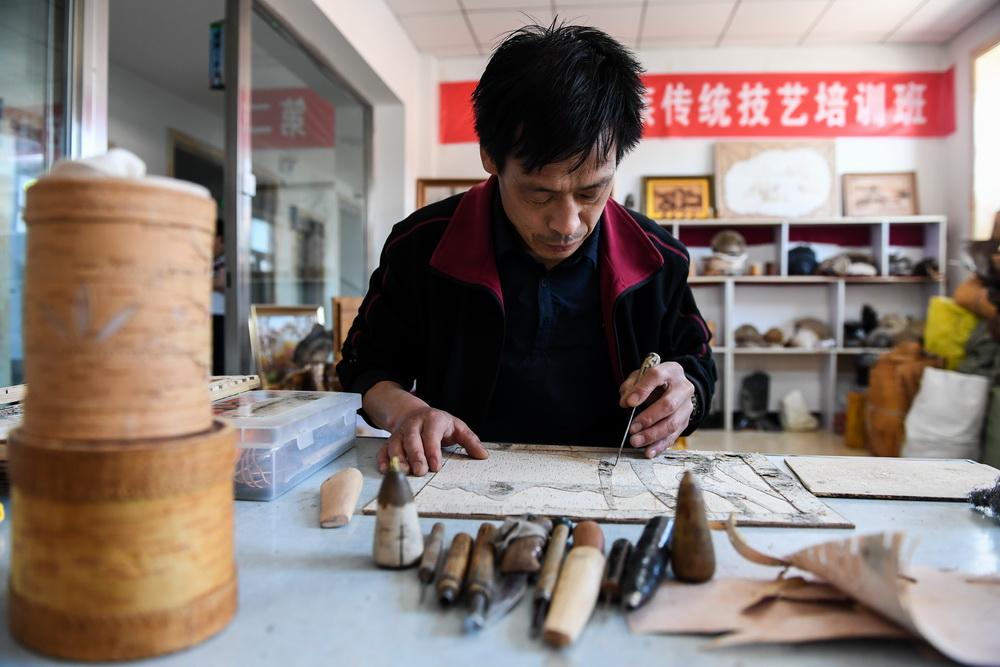 6月7日,在内蒙古自治区根河市的工作室里,王跃辉在桦树皮上加工雕刻图案。