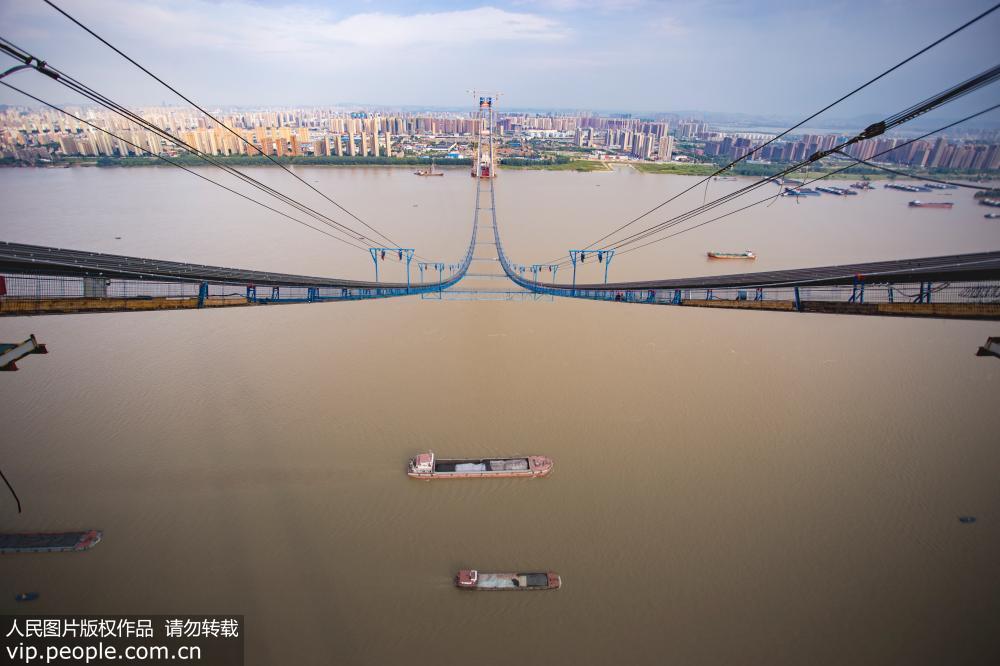 """武汉:世界跨度最大双层悬索桥建设忙 酷暑下工人来回在""""云端""""穿梭"""