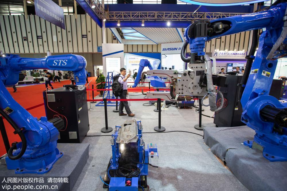 10月11日,观众在2018世界智能制造大会展示区参观点焊机器人。