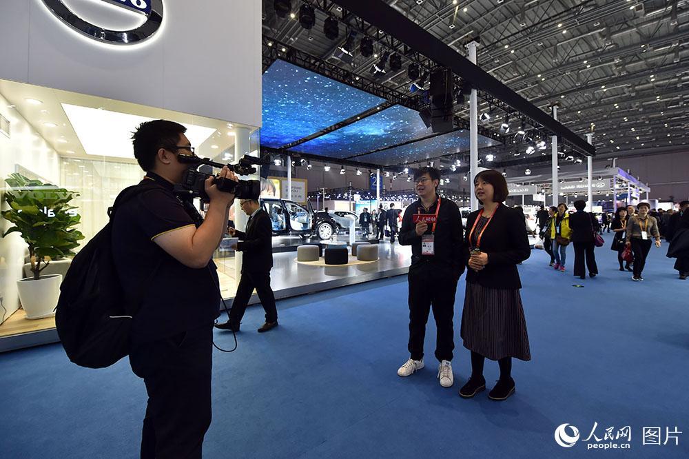 11月7日,在进博会展区,人民网记者正在进行视频直播。(人民网记者 翁奇羽 摄)