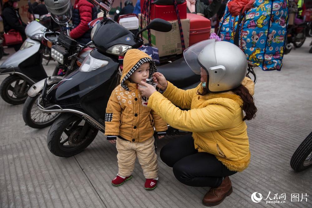 2019年1月25日,广东肇庆,鼎湖山服务区。一位妈妈给孩子喂粥。骑行路途虽然艰辛,但沿途交管部门和爱心企业设立许多补给站为骑行回家的工友提供服务。