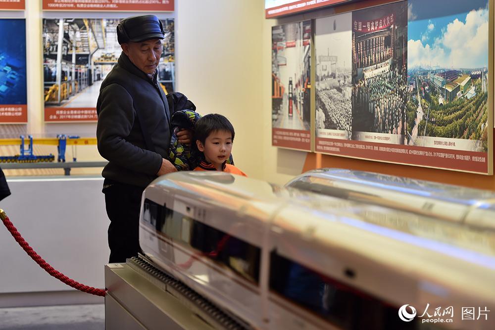 2月1日,小朋友在家人的陪同下,参观和谐号与复兴号列车模型。(人民网记者 翁奇羽 摄)