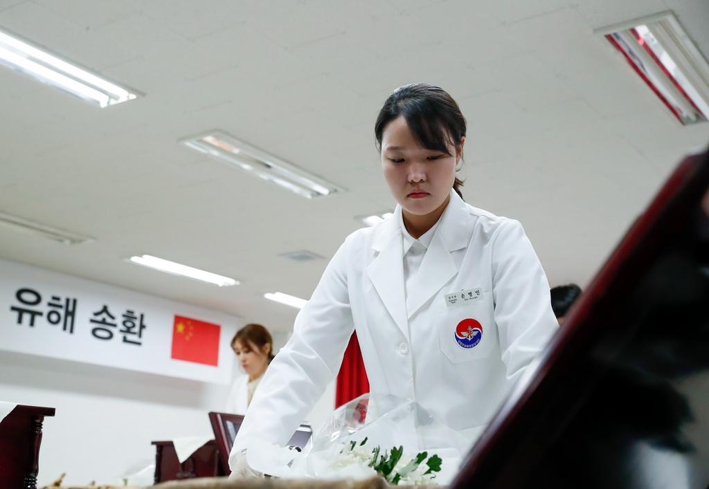 4月1日,韩方工作人员准备将志愿军烈士遗骸入殓。新华社记者 王婧嫱 摄