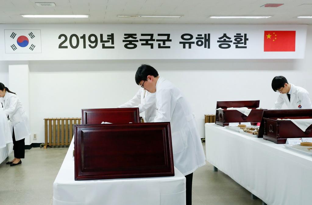 4月1日,韩方工作人员将志愿军烈士遗骸入殓。  新华社记者 王婧嫱 摄