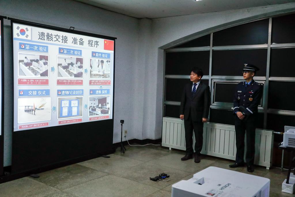 4月1日,韩国国防部遗骸发掘鉴定团身份确认中心负责人张有亮(左)在仪式开始前介绍遗骸交接的准备程序。 新华社记者 王婧嫱 摄