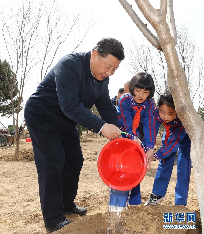4月8日,党和国家领导人习近平、栗战书、汪洋、王沪宁、赵乐际、韩正、王岐山等来到北京市通州区永顺镇参加首都义务植树活动。这是习近平同少先队员一起给刚栽下的树苗浇水。 新华社记者 鞠鹏 摄