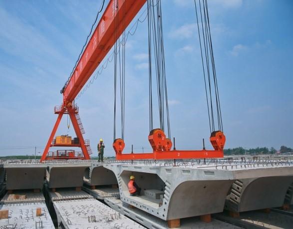 图为工人在进行节段梁吊装作业。