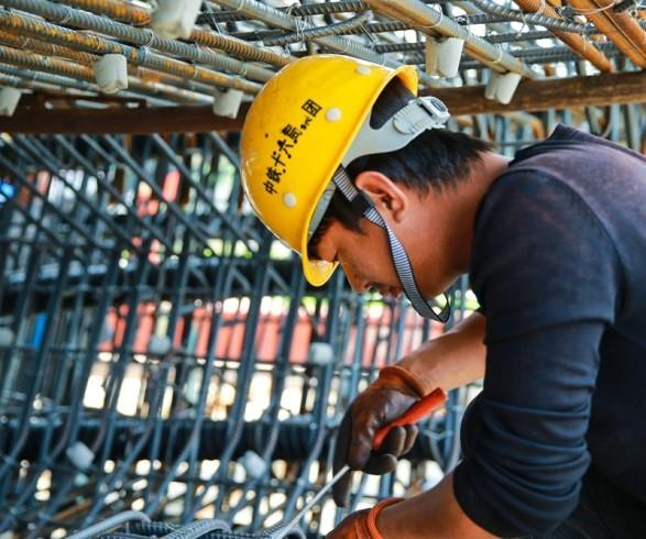 图为工人在绑扎节段梁钢筋。
