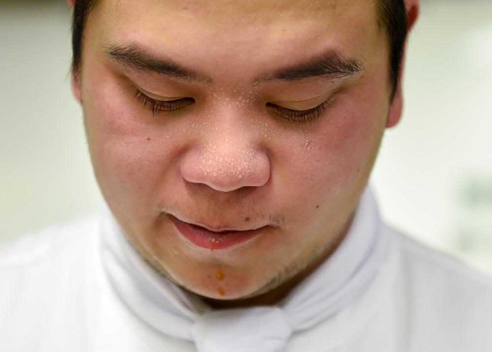 5月13日,在新西兰首都惠灵顿理工学院,一名西厨班学员鼻上渗出汗珠。