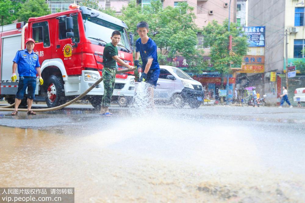 6月12日,江西省峡江县消防队员正在巴邱镇冲洗街道。