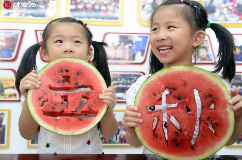 """8月6日,安徽省合肥市滨湖欣园社区的一对双胞胎正在参与""""啃秋"""",体验中国传统民俗。"""