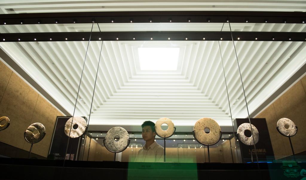 在位于浙江省杭州市的良渚博物院,观众参观良渚文化遗址出土的玉璧(6月22日摄)。