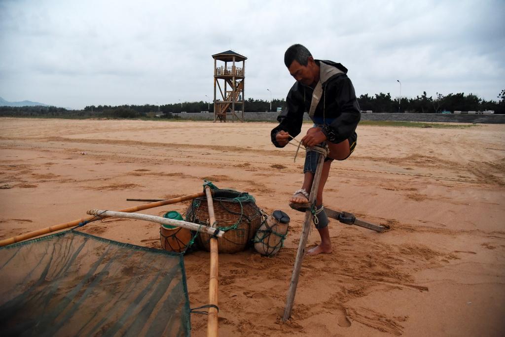 9月2日,渔民在下海前将木棍调试准备好。