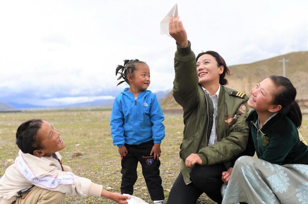 坚热益西(右二)在牧区和弟弟妹妹一起放飞纸飞机(7月13日摄)。新华社记者 普布扎西 摄