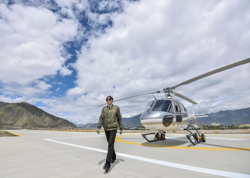 坚热益西从直升机前走过(8月7日摄)。新华社记者 晋美多吉 摄