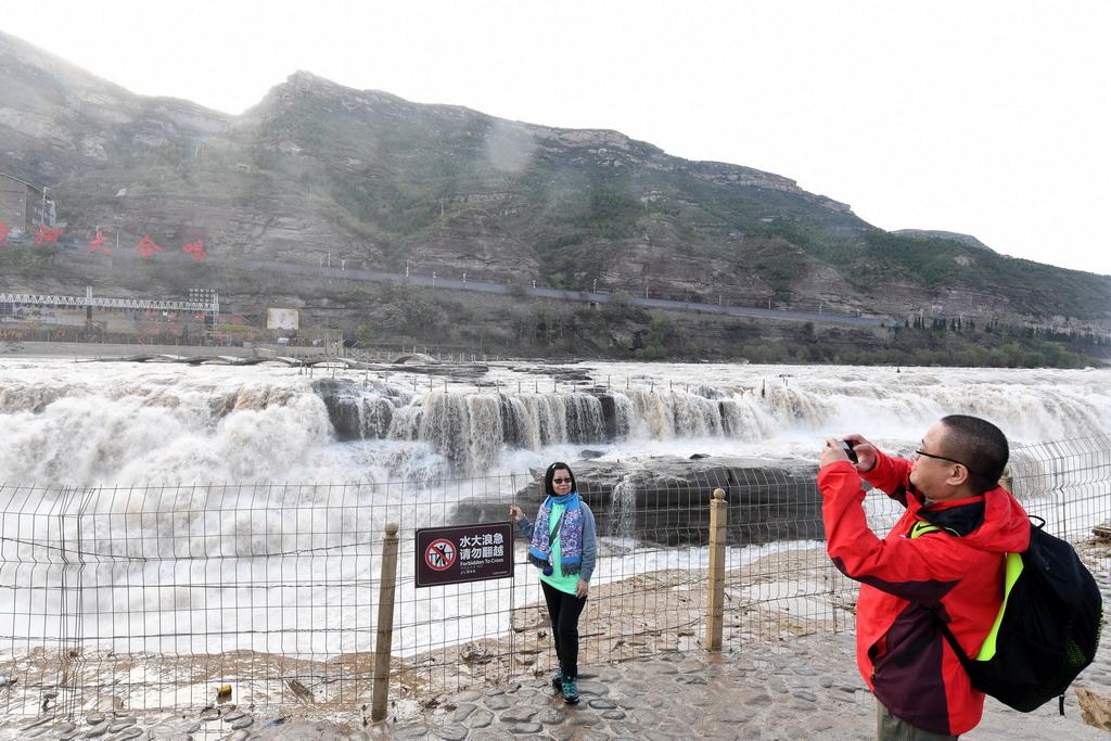 10月17日,游客在位于山西吉县的壶口瀑布前拍照。