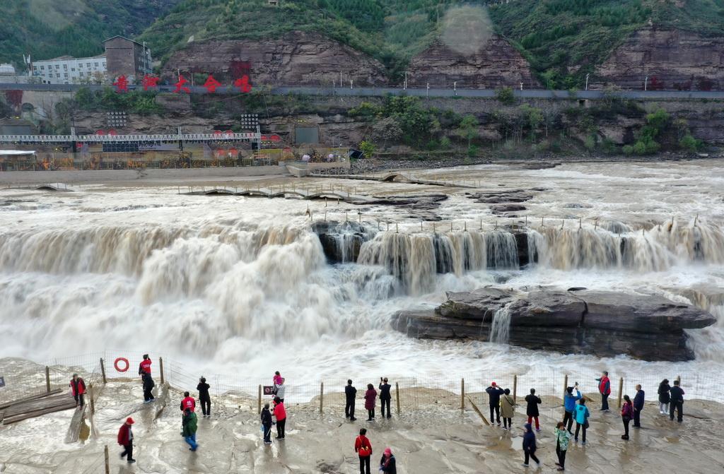 10月17日,游客在位于山西吉县的壶口瀑布参观(无人机拍摄)。