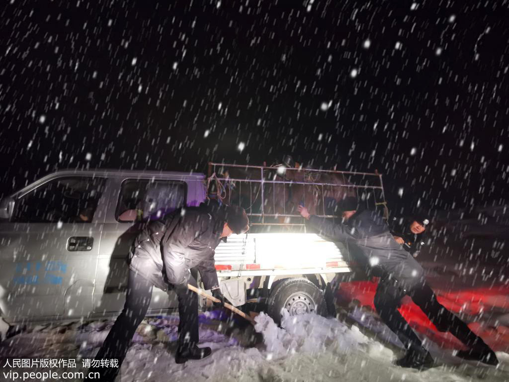 12月17日,新疆阿勒泰边境管理支队阿热勒边境派出所民警正在用铁锹挖积雪。