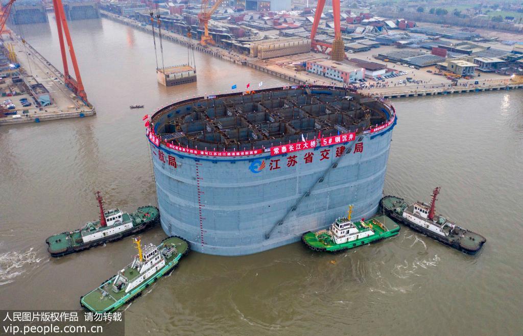 12月28日,多艘拖船将常泰长江大桥第5号墩钢沉井拖入长江航道(无人机拍摄)。