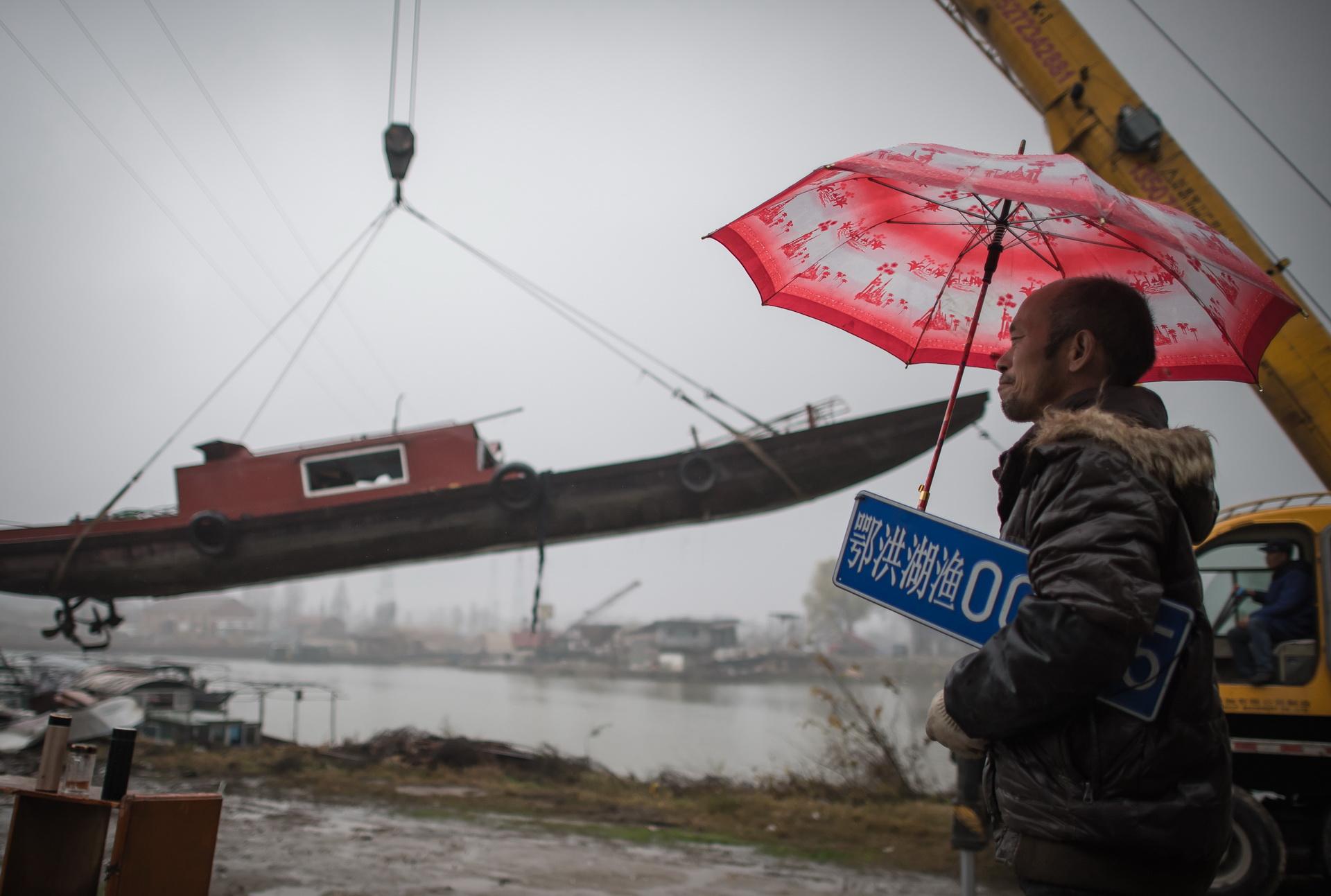 在长江新螺段白�D豚国家级自然保护区渔船拆解现场,长江捕捞村渔民夏明星注视着被吊起的渔船,他手上的渔船编号牌也即将被收回(2019年12月25日摄)。