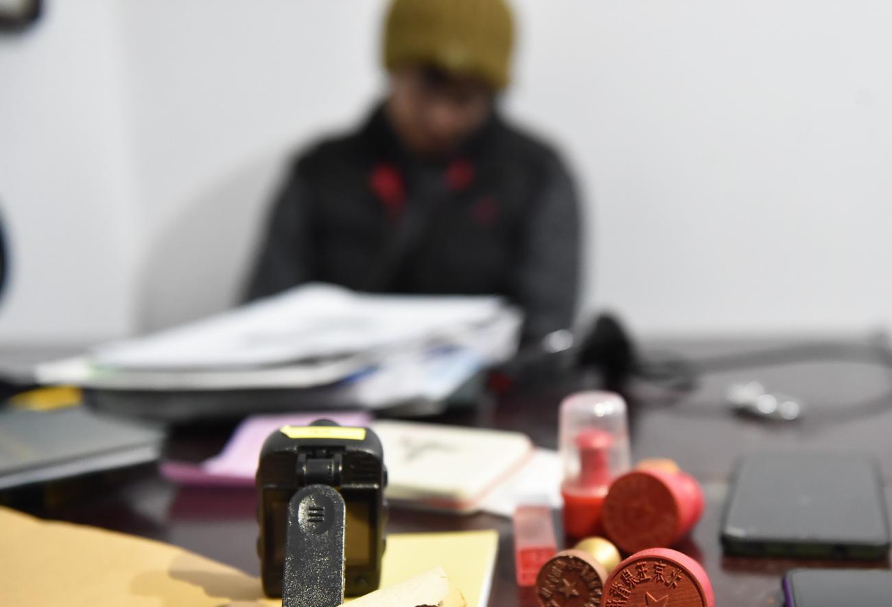 1月7日,在查扣抓捕现场,一名犯罪嫌疑人坐在被查扣的印章等物证前。