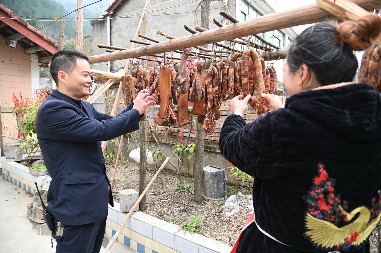 车站站长和炊事员察看制作的腊肉香肠