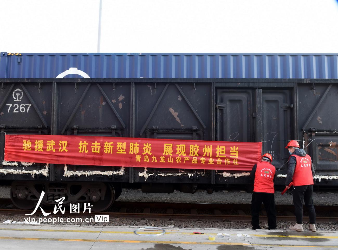 1月29日,位于山东胶州市的上合示范区中铁联集青岛中心站里,两名志愿者在列车上挂横幅。