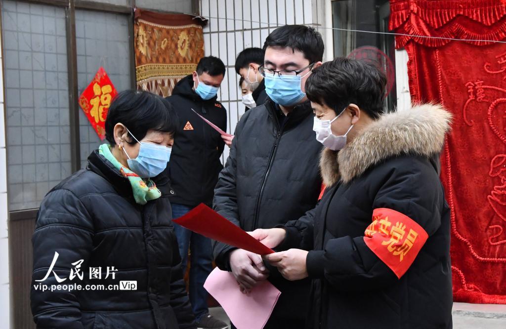 1月28日,在河北省邯郸市永年区小龙马乡郑营村,党员干部谢彩霞(右一)和党员干部梁豹(右二)以及志愿者正在为村民宣传防疫知识。(胡高雷  人民图片)