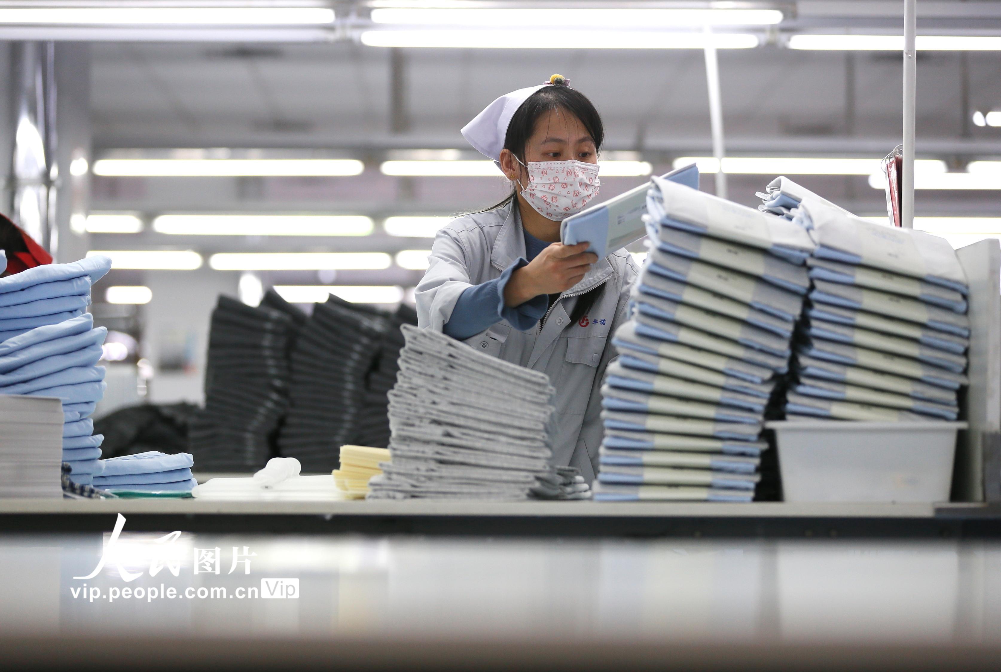2020年2月14日,在位于山东青岛市即墨区的青岛即发集团有限公司生产车间里,工人在包装出口到海外的服装产品。