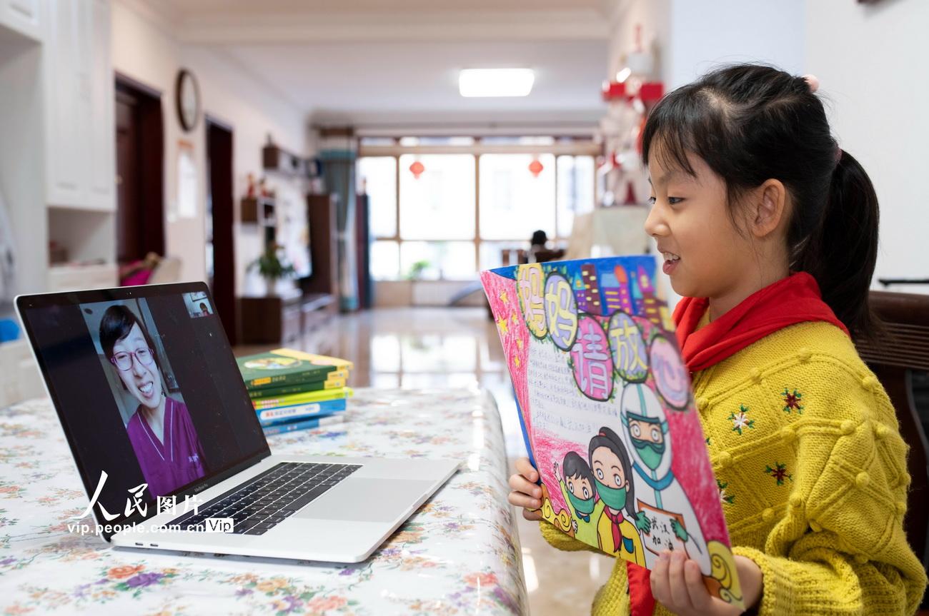 3月1日,呼和浩特市赛罕区敕勒川绿地小学学生杨艺冉在空中开学礼上与驰援武汉医疗队的妈妈进行视频通话。