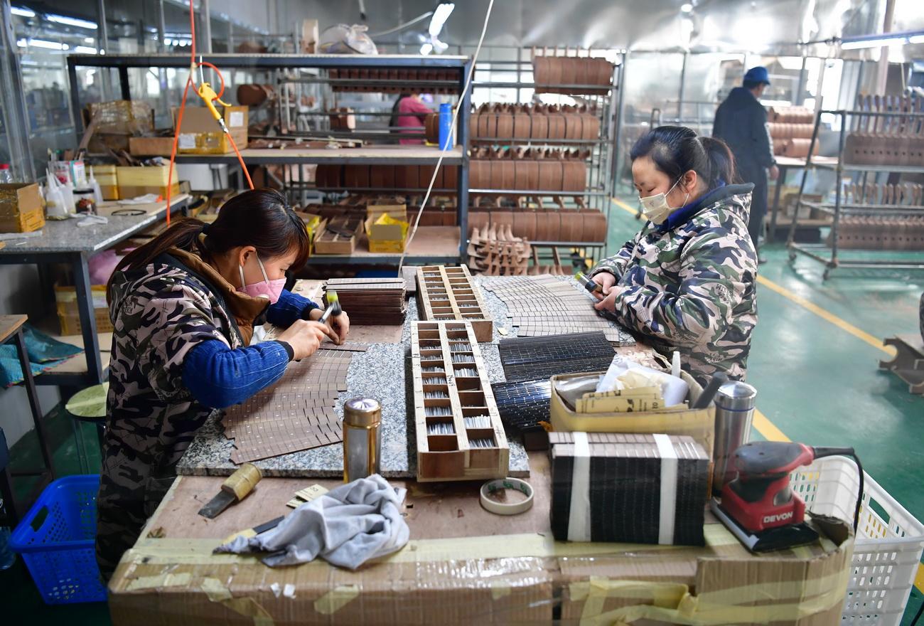 3月12日,在城固县博望街道办事处江湾社区一乐器厂车间内,工人在制作乌克丽丽的指板。