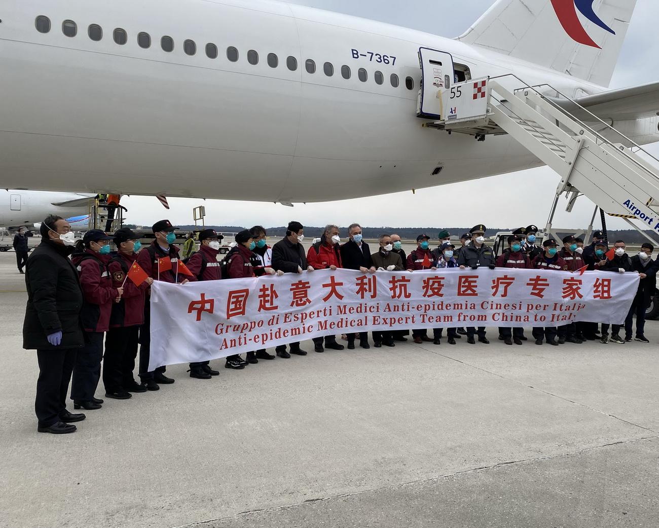 3月25日,在意大利米兰马尔奔萨机场,中国第三批赴意大利抗疫医疗专家组成员与意方人员合影。