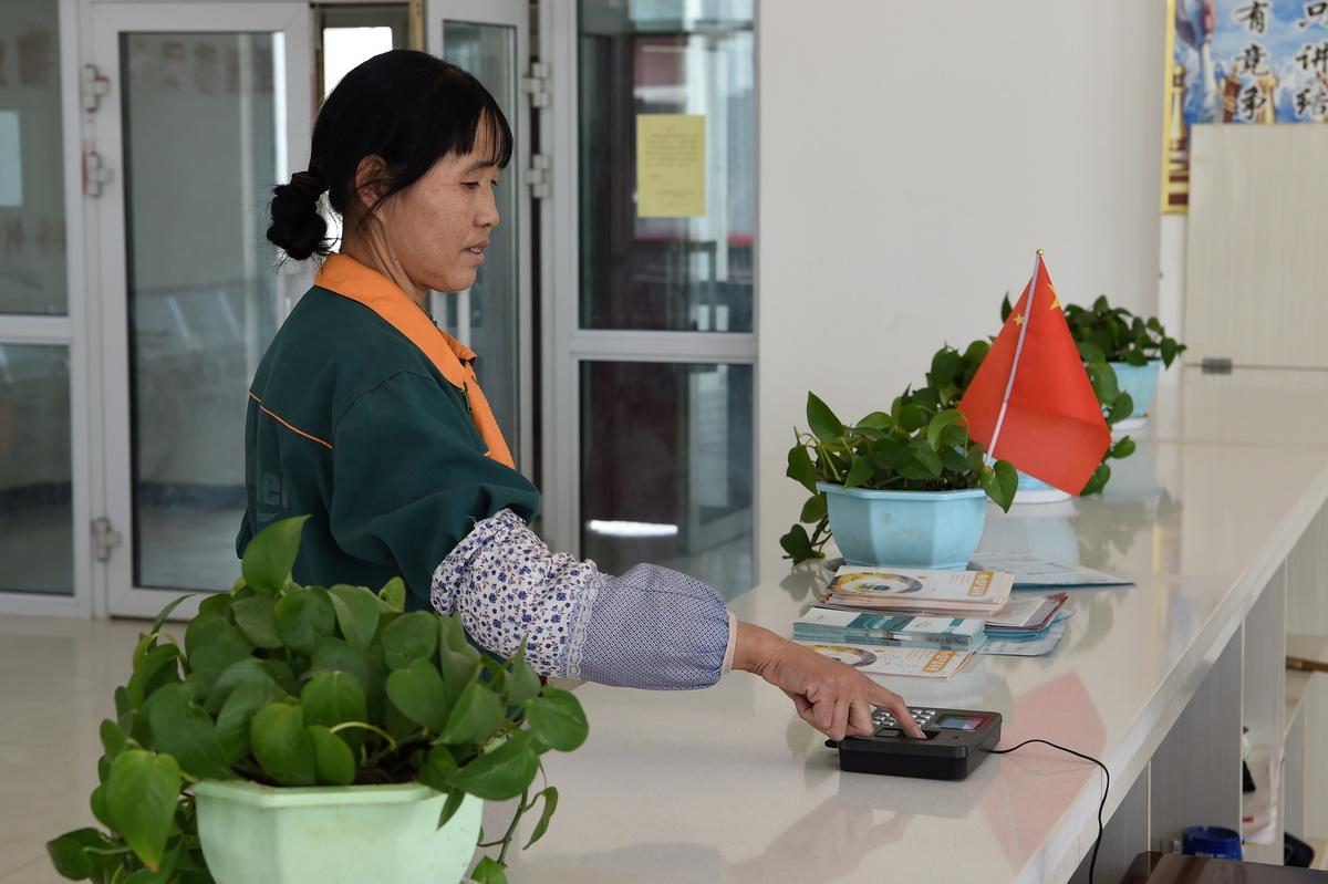 在古浪县绿洲生态移民小城镇物业服务中心,胥存上班前进行指纹打卡(4月7日摄)。